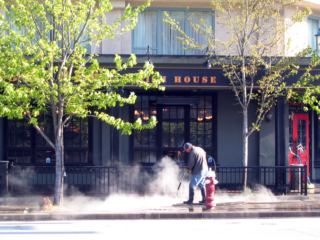MCA team cleaning exterior side walk with steam